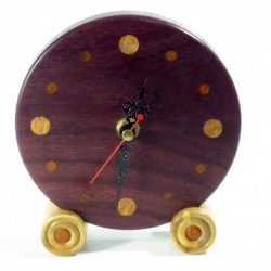 Approximately 136mm in diameter. A fine piece of craftsmanship a handmade cheeky wooden clock for the desk, mantle or shelf. This is the real colour of the wood and has not been altered in any way, it will enrich with age. The clock hands are of course RoHS approved and tested and come complete with full instructions. Designed and made by me in Shropshire - not mass produced; each of my Tommy Woodpecker Woodworks clocks is slightly different and unique, beautifully and lovingly finished with beeswax polish so the natural colour of the wood can speak for itself! An ideal gift for anyone who loves the unique richness and quality of the grain and colours of natural finely crafted wooden items. A special, memorable gift for a wedding, anniversary, housewarming, leaving or retirement gift for someone very special. All clocks are carefully packaged to ensure they reach you safely and have labels and care instructions, ideal for any gift. 1 x AA Battery operated, battery included for UK only not included for overseas, batteries cannot be airmailed. Care Instructions To set the time, do not push the hands of the clock around, use the white dial on the back of the clock mechanism to alter the time. To dust the clock, avoid damaging the hands by gently dusting one half of the clock face at a time, when the hands are clear of the area, then repeat for the other half of the clock face when the hands are clear of that area. The battery can be taken out for cleaning to stop the clock at any time. Occasionally a slightly damp cloth can be used if necessary. The wood will benefit from a little gentle application of beeswax once a year and will reward you with a continued shine.